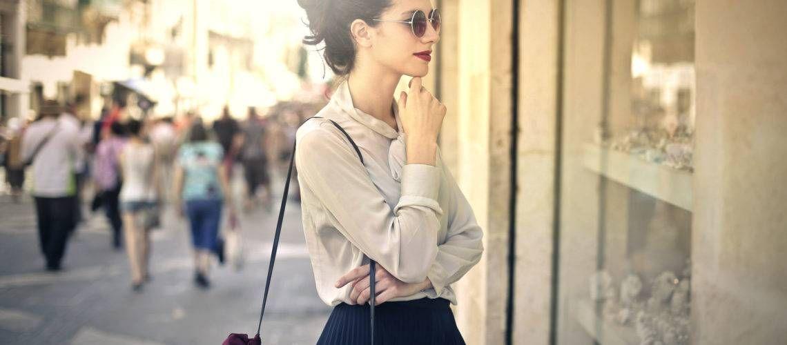 mulher olhando vitrine de loja na rua