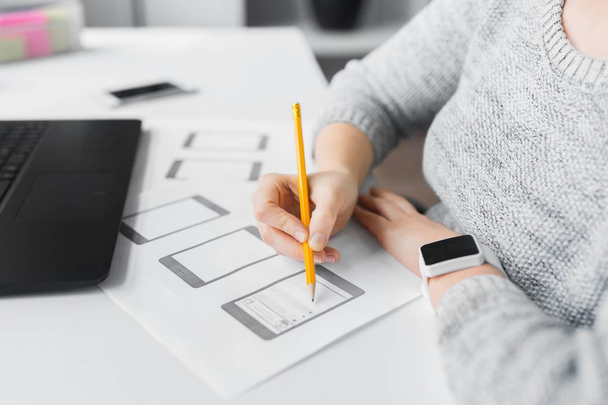 Mulher com lápis na mão desenhando protótipo de aplicativo para celular.